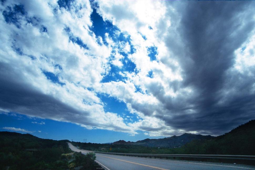 Free image of Broken clouds above a two lane road through rural Arizona.