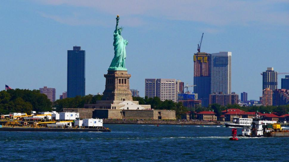 Download Free Stock HD Photo of Staute of Liberty with city background Online