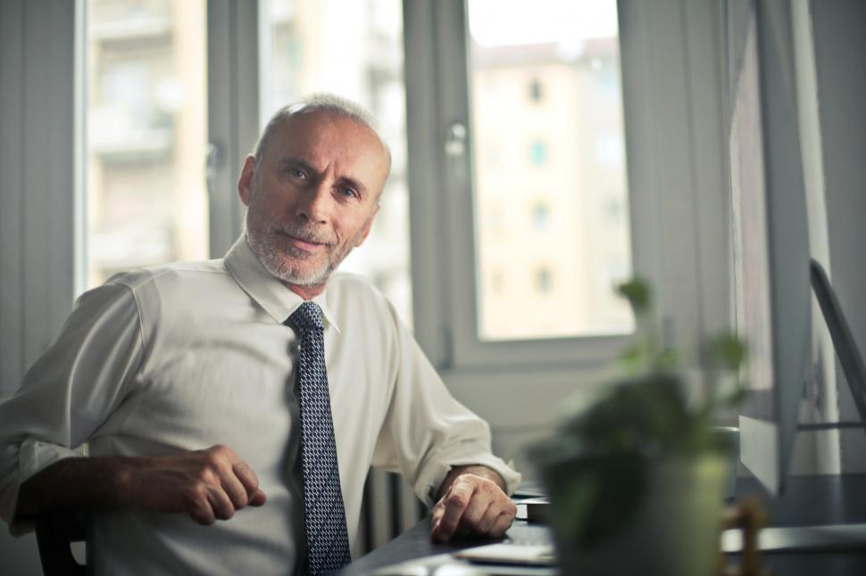 Download Free Stock HD Photo of Man Sitting on Chair Beside Table in office Online