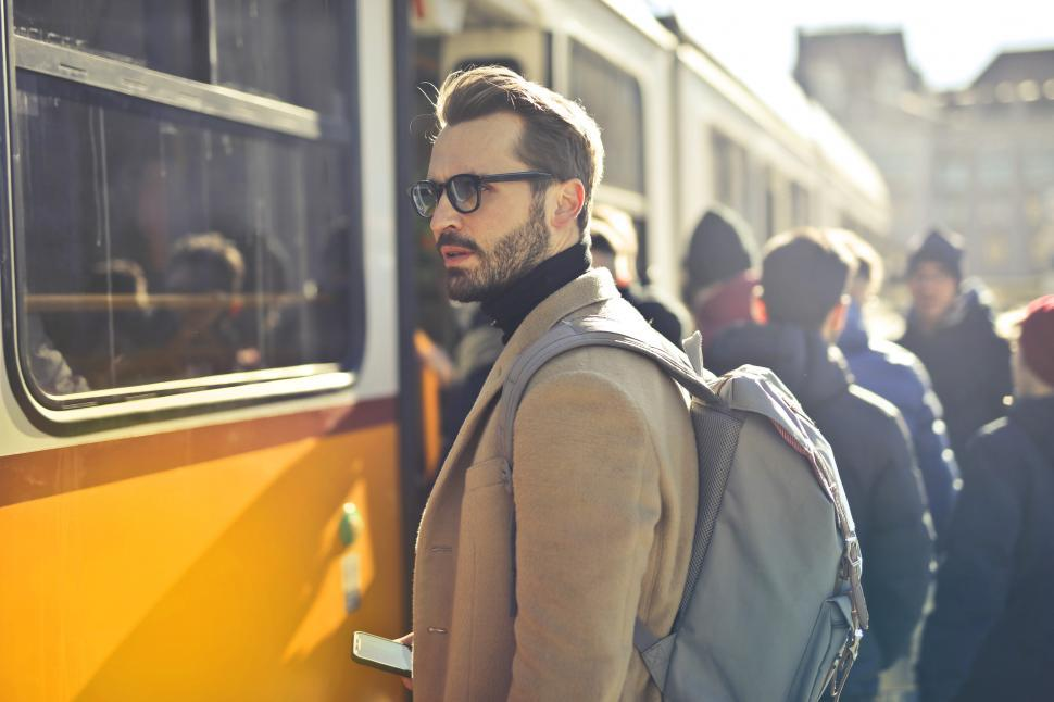 Download Free Stock HD Photo of Young Adult man in eyeglasses waiting for the train at tram stat Online