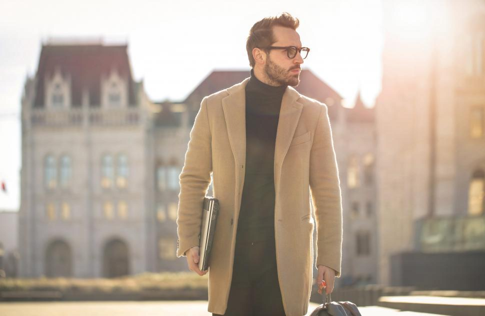 Download Free Stock HD Photo of Young adult bearded male with eyeglasses,walks on street with la Online