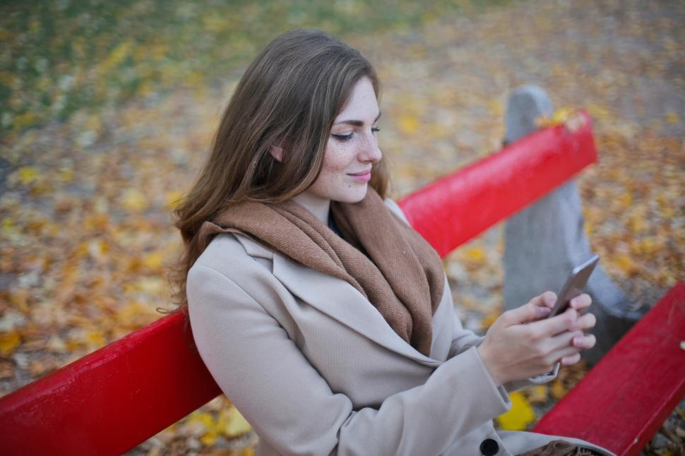 Download Free Stock HD Photo of Young Woman In Scarf And Beige Jacket Holding Cellphone While Si Online
