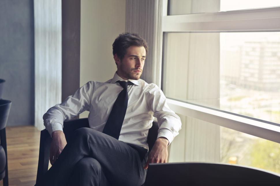Download Free Stock HD Photo of Young man in white shirt and black tie sitting near window durin Online