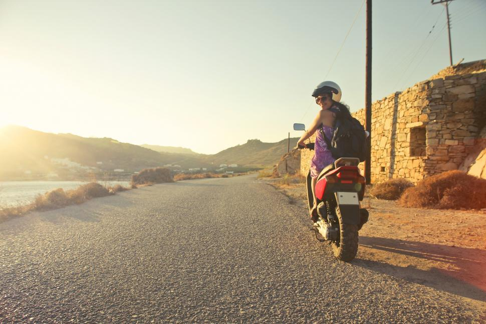 Download Free Stock HD Photo of Young Girl riding a motorcycle on an empty Asphalt Road Online
