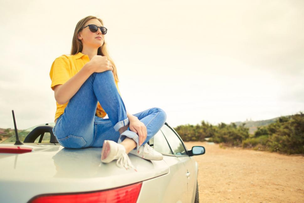 Download Free Stock HD Photo of Young Woman Wearing Yellow Shirt and Blue Denim Jeans Sits on Si Online
