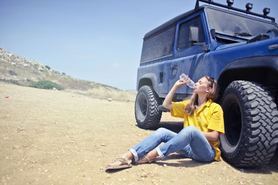 Download Free Stock HD Photo of Young Woman Drinking Water From Bottle While Sitting Besides SUV Online