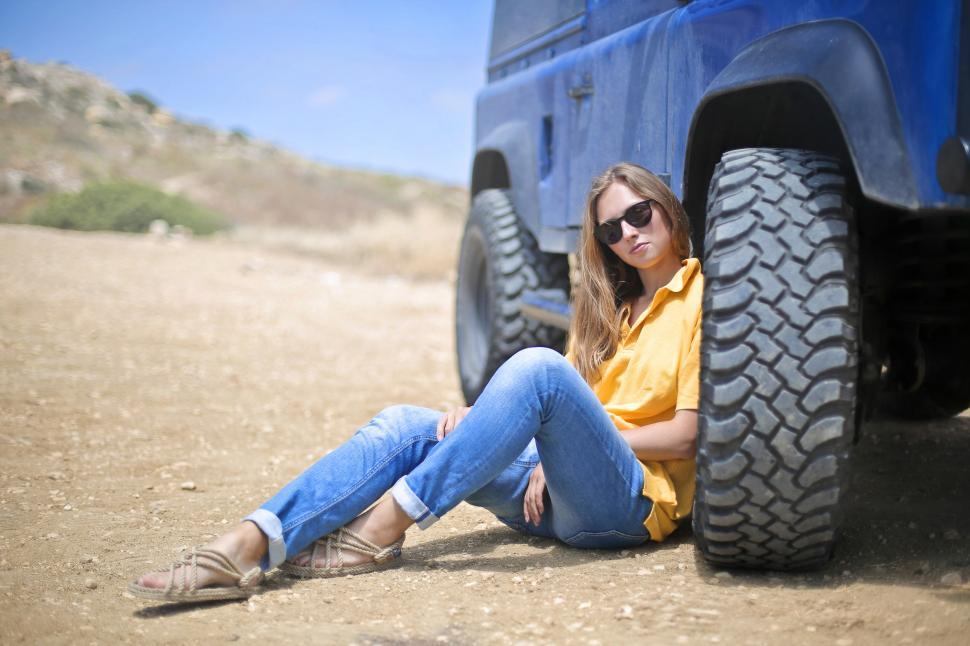 Download Free Stock HD Photo of Young Woman In Yellow Polo Shirt Sitting Besides SUV Tyre  In Th Online