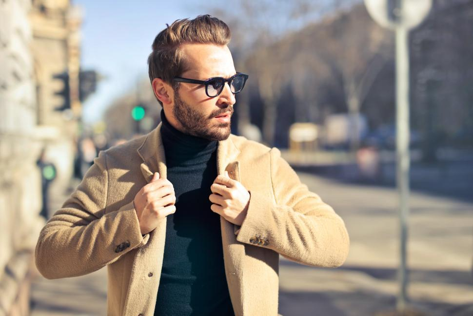 Download Free Stock HD Photo of Young Adult Man wearing beige jacket and sunglasses posing on th Online