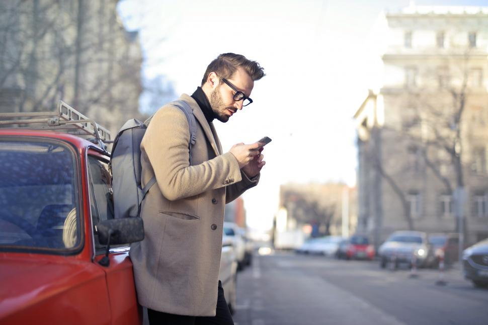 Download Free Stock HD Photo of Man in Beige Coat Holding Phone Leaning on Red Vehicle Online