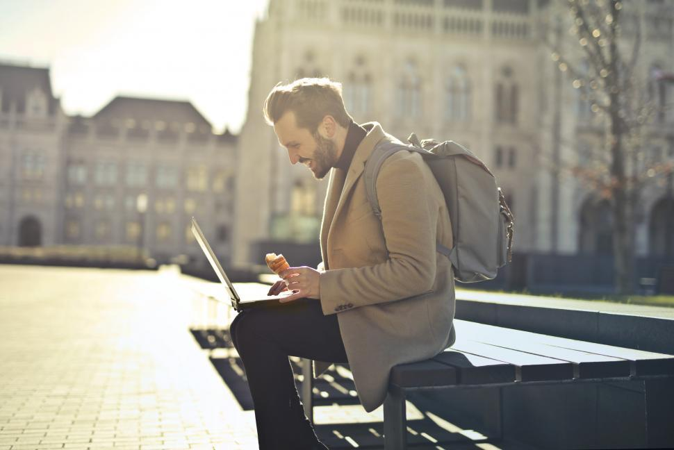 Download Free Stock HD Photo of Young Adult Man using a laptop while sitting on a bench during a Online