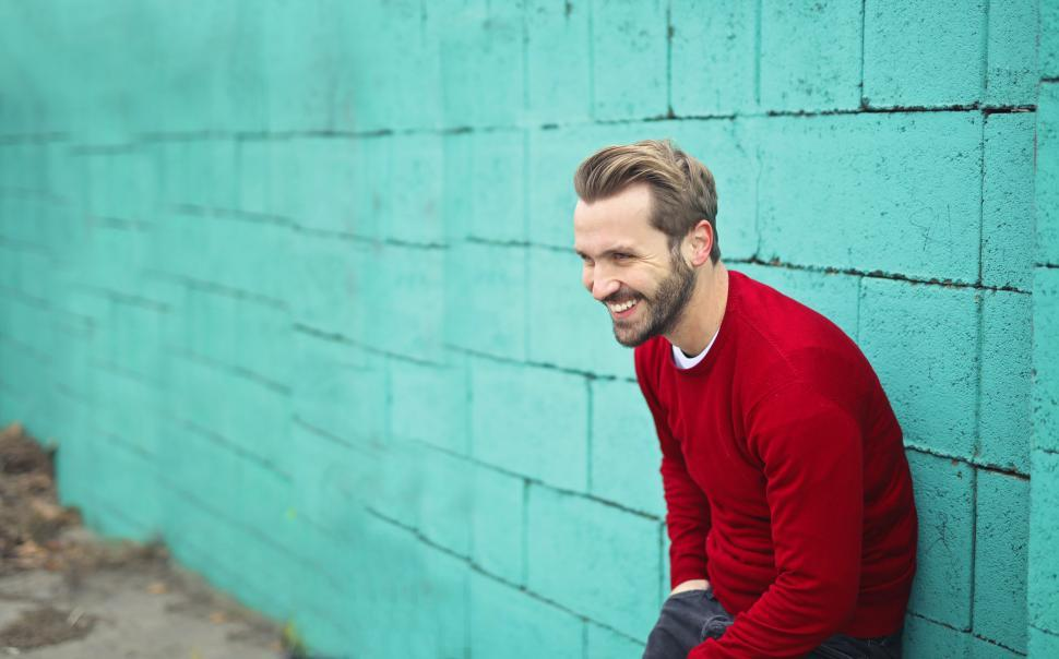 Download Free Stock HD Photo of Young Man Wearing a Red Sweater, Smiling and Leaning on a Blue W Online