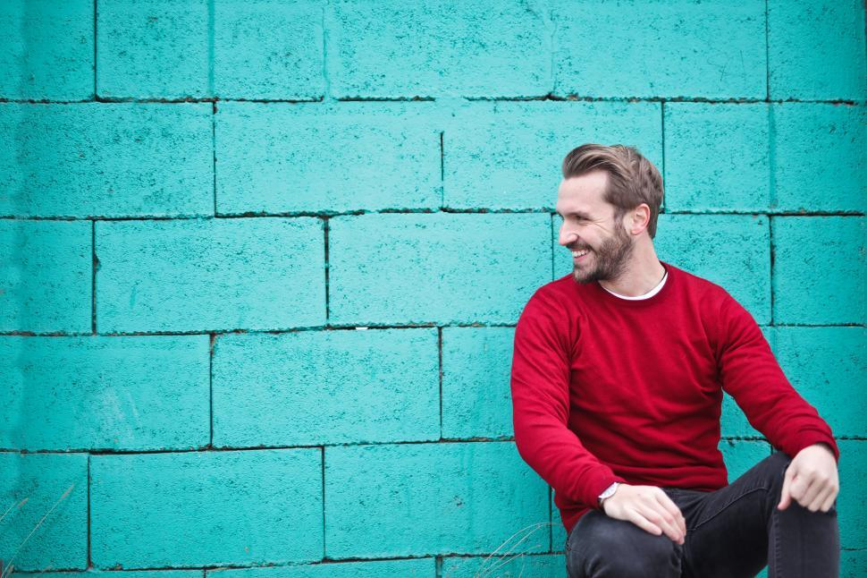 Download Free Stock HD Photo of Young Man wearing red sweatshirt and black pants leaning on the Online