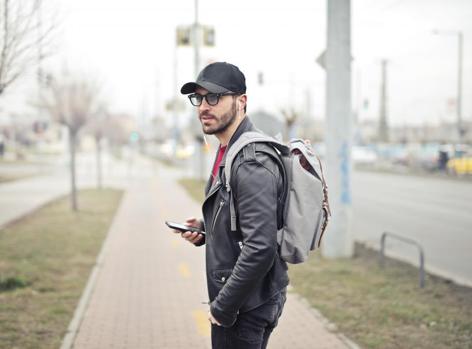 Download Free Stock HD Photo of Young Adult man wearing black leather jacket holding smartphone Online