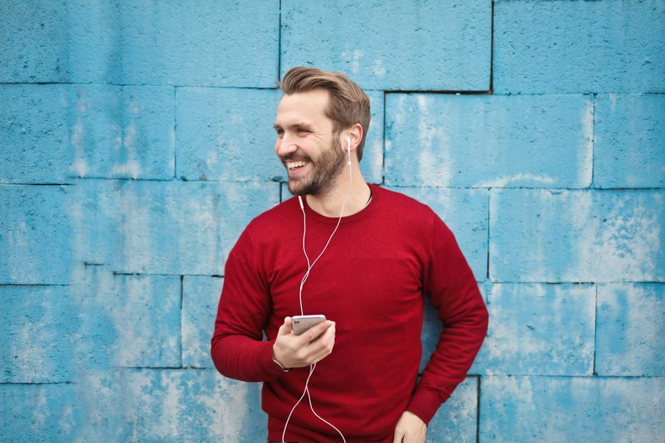 Download Free Stock HD Photo of Young man listening to music in his cellphone against turquoise Online