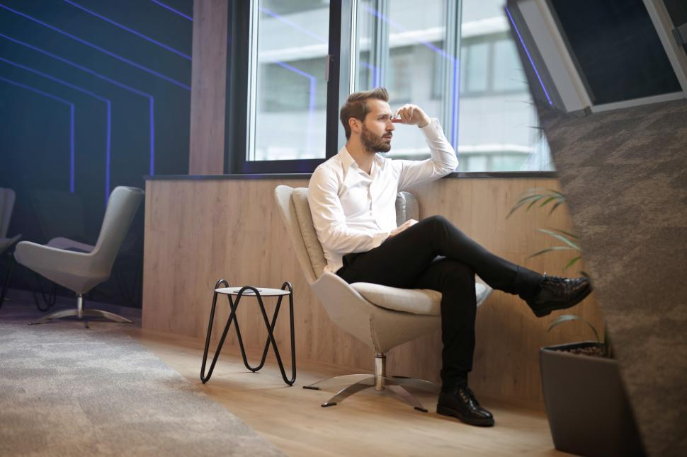 Download Free Stock HD Photo of Young Adult man sitting on office chair, thinking and consideri Online