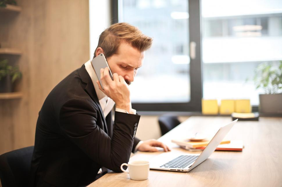 Download Free Stock HD Photo of Young Adult Man Having a Phone Call In-front of a Laptop Online