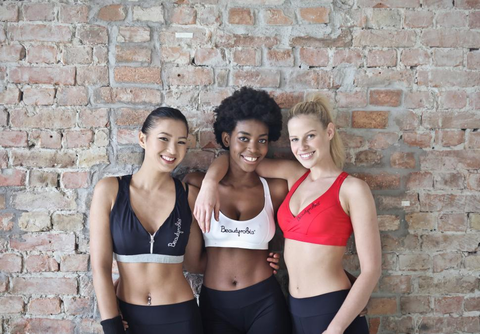 Download Free Stock HD Photo of Three Young Woman Wearing Red, White and Black Sports Bra Posing Online