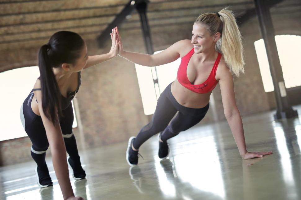 Download Free Stock HD Photo of Two happy beautiful young athletic women exercising together wit Online
