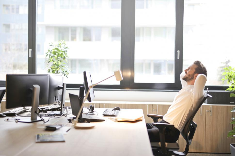Download Free Stock HD Photo of Young Adult Man In White Shirt Laughing While Sitting on Office Online