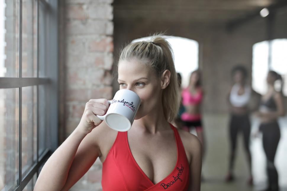 Download Free Stock HD Photo of Young Woman Wearing Red Tank Top drinking a cup of coffee Online