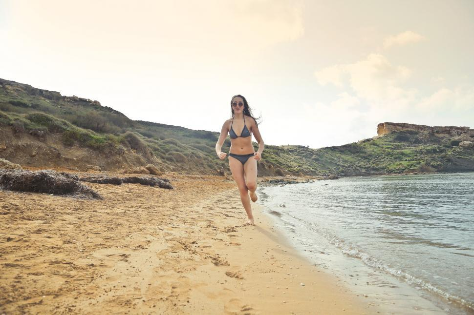 Download Free Stock HD Photo of Woman Wearing Grey Bikini Running On White Sand at Seashore Online