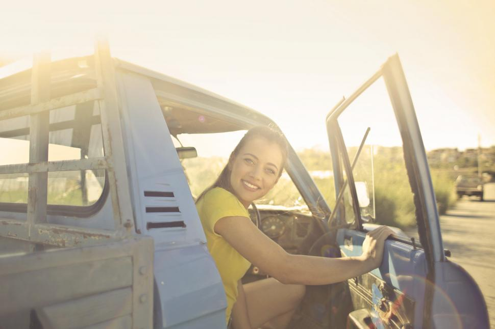 Download Free Stock HD Photo of Young beautiful woman coming out of pick up truck driving seat Online