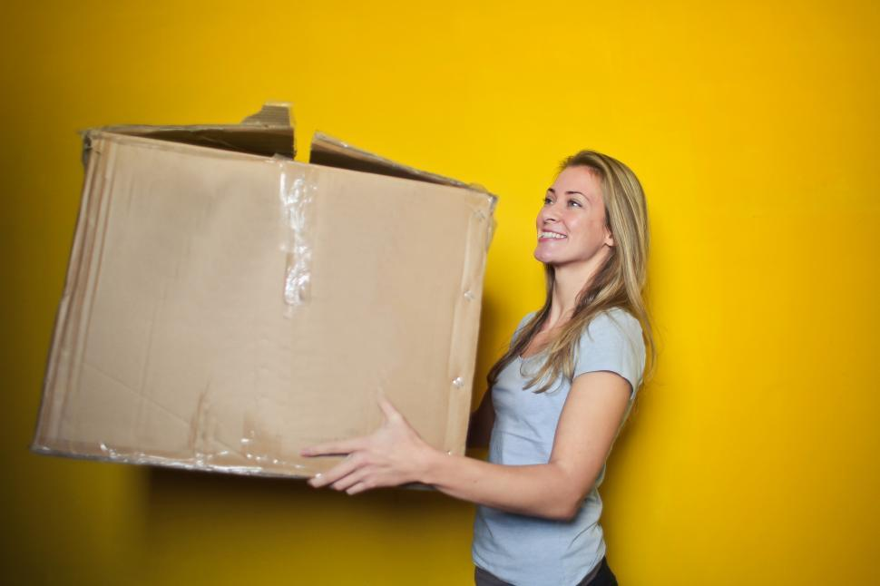 Download Free Stock HD Photo of Young Woman Holding Brown Cardboard Box Online