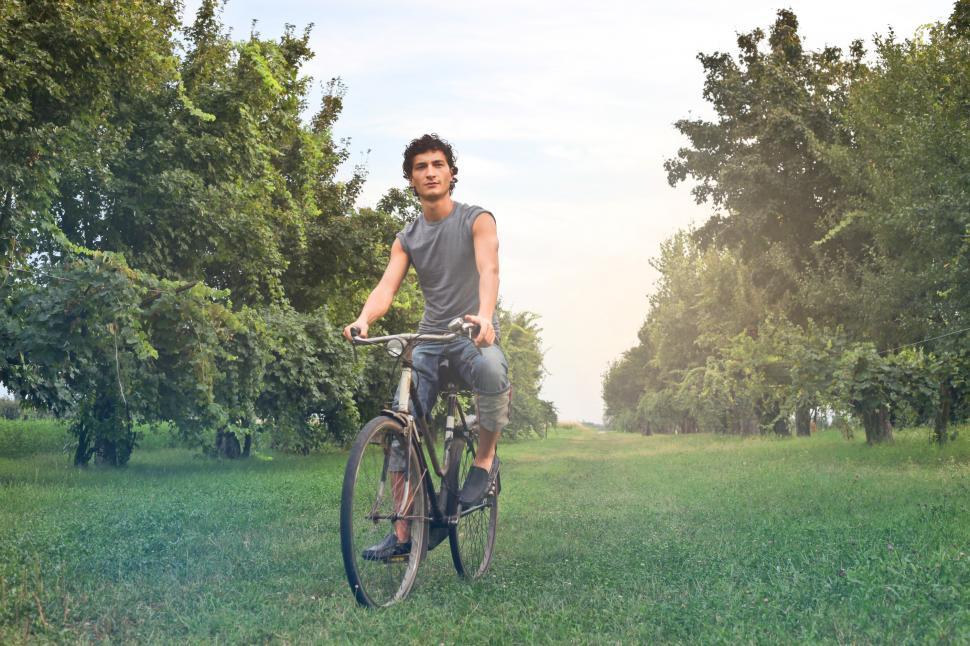 Download Free Stock HD Photo of Young Farmer Riding A Bicycle In The Meadow Online