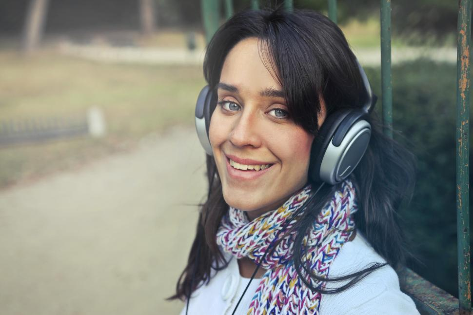 Download Free Stock HD Photo of Young Woman with headphones listen to the music in the park Online