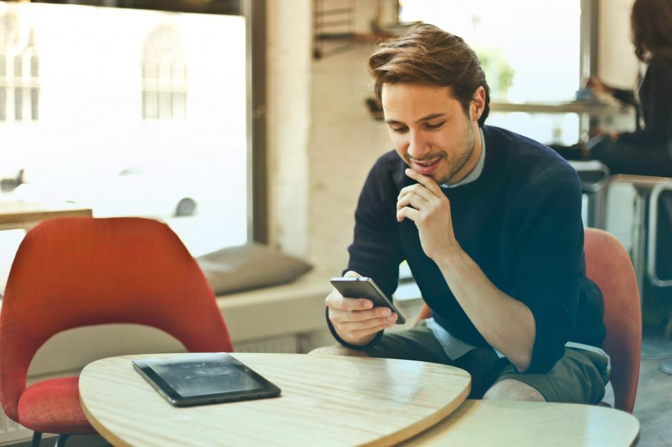 Download Free Stock HD Photo of Young Man In Black Sweater Using His Smartphone While Sitting In Online