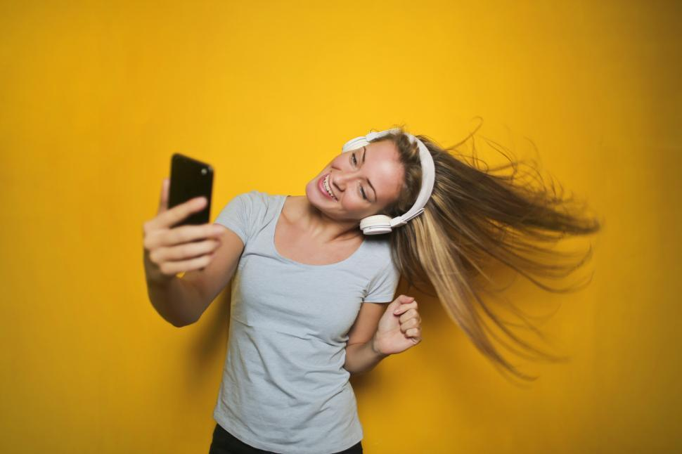 Download Free Stock HD Photo of Excited woman dancing and listening music with wireless headphon Online