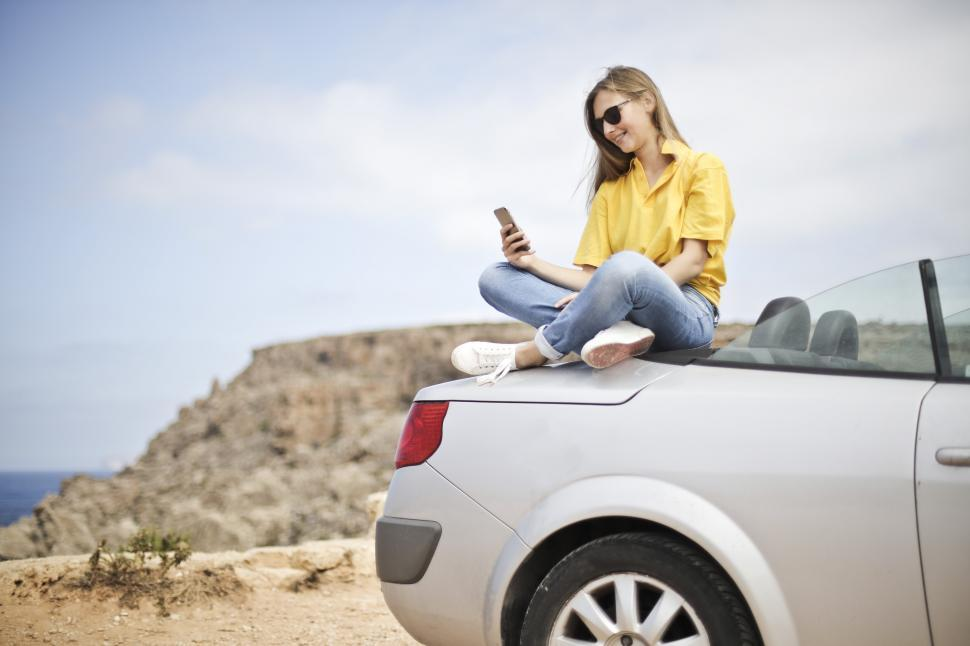 Download Free Stock HD Photo of Young Woman in Yellow Shirt and Denim Jeans Using Smartphone on Online