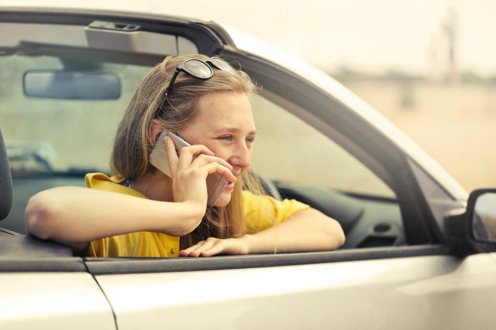 Download Free Stock HD Photo of Young Woman Wearing Half-Sleeved Yellow Shirt Talking On Phone Online