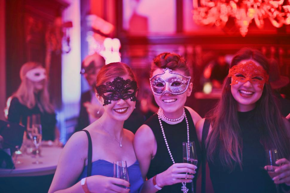 Download Free Stock HD Photo of Three Women In Masks Holding Wine Glasses In Nightclub Online