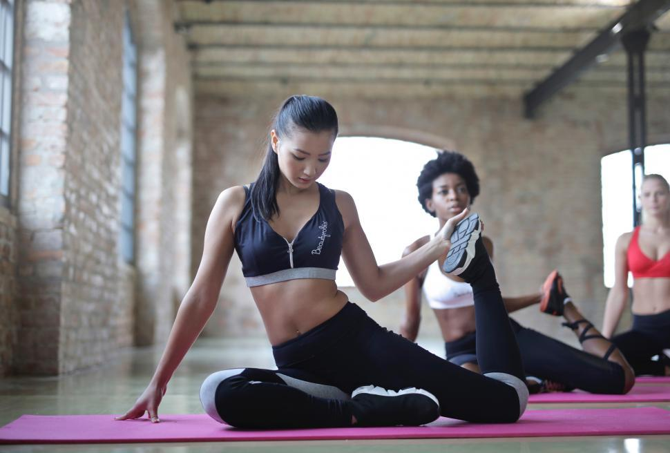 Download Free Stock HD Photo of Three young multi ethnic  women doing yoga on mat Online