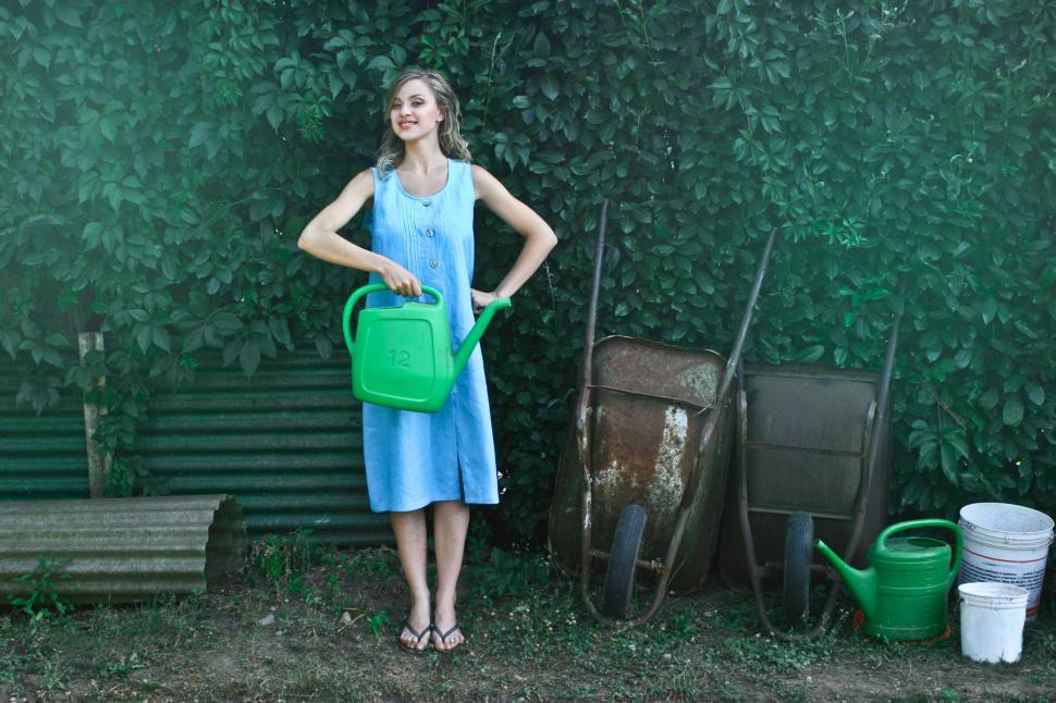 Download Free Stock HD Photo of A beautiful young woman holding a plant watering can in the gard Online