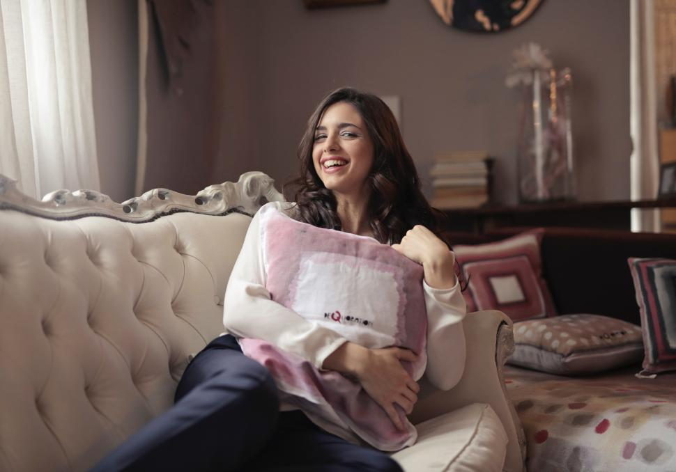 Download Free Stock HD Photo of A beautiful young woman with a smiling face embracing the cushion Online