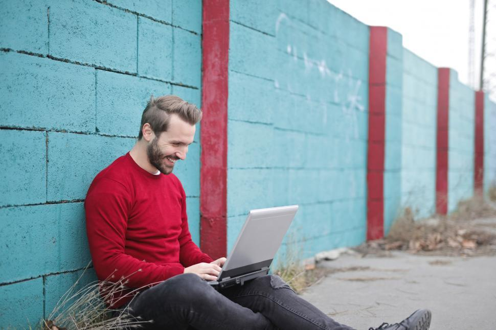 Download Free Stock HD Photo of A young bearded man sitting against a wall working Online