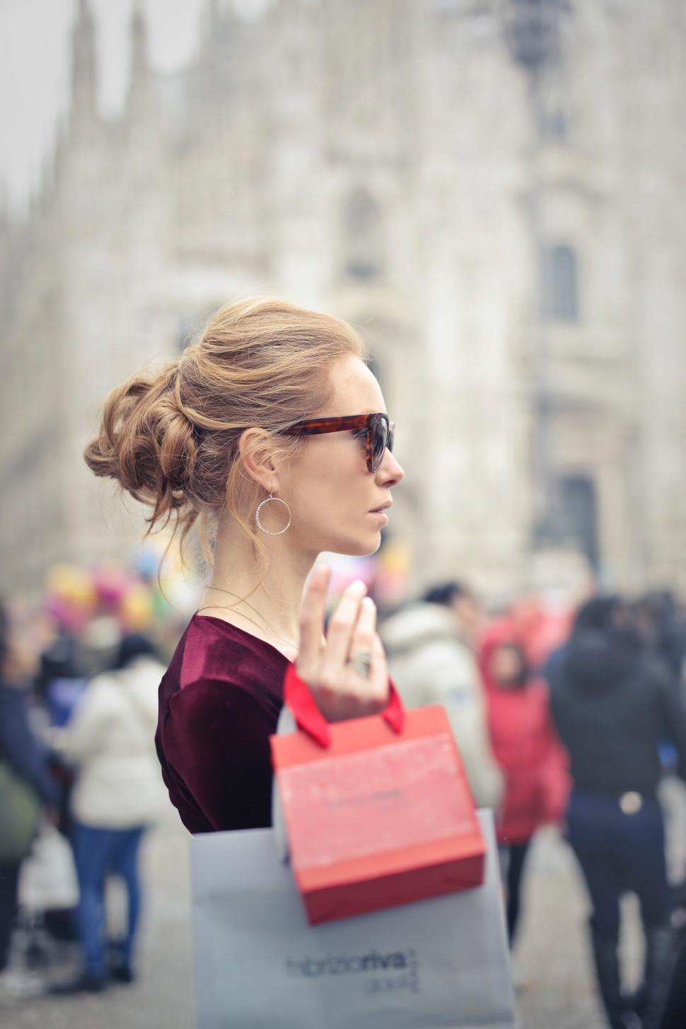 Download Free Stock HD Photo of A young blond woman with elegant hair bun holding shopping bags Online