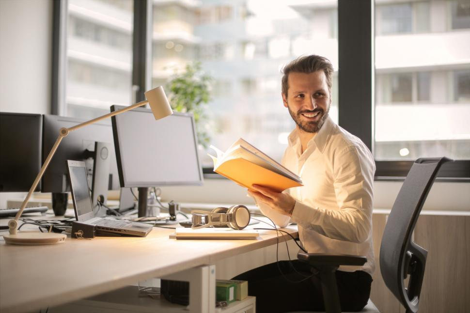 Download Free Stock HD Photo of A young man smiling while holding notebook in his hands Online