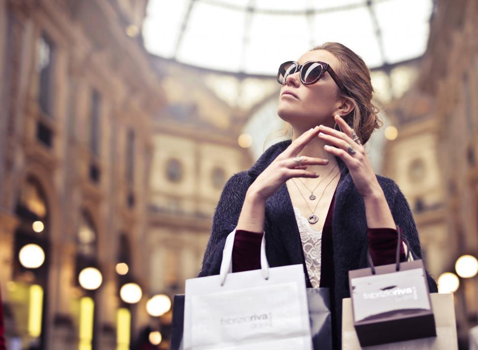 Download Free Stock HD Photo of A young blond woman with elegant hair bun posing with shopping b Online