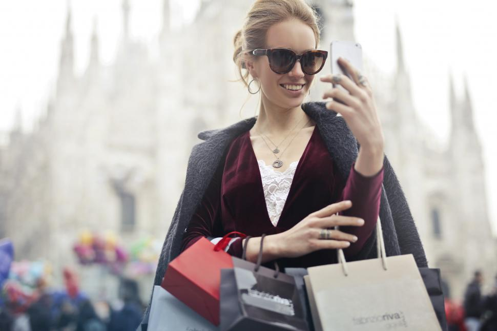 Download Free Stock HD Photo of A young blond woman looks at her mobile phone holding while shop Online