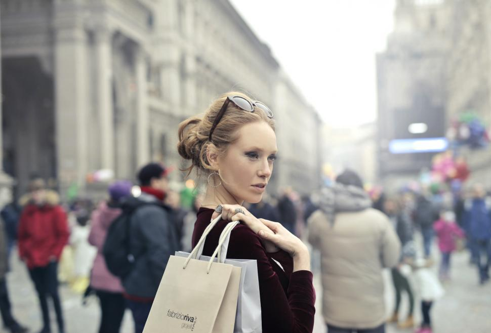 Download Free Stock HD Photo of A young blond woman holding shopping bags in her hands on her sh Online