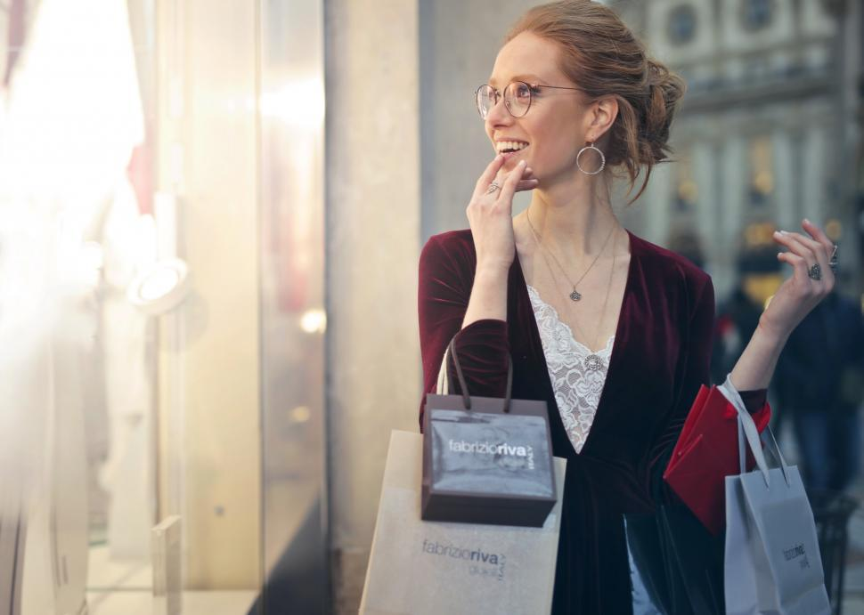Download Free Stock HD Photo of A young blond woman holding shopping bags in her hands Online