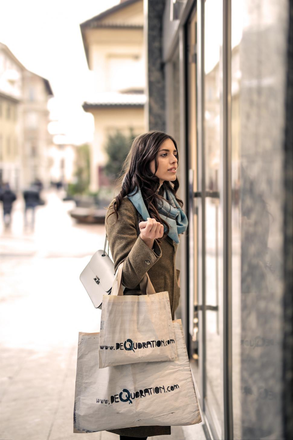 Download Free Stock HD Photo of A young woman holding shopping bags in her hand Online