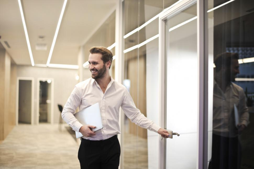 Download Free Stock HD Photo of A young bearded caucasian man entering a glass cabin Online