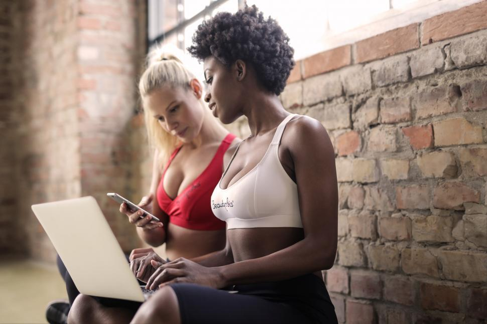 Download Free Stock HD Photo of Two multiethnic women wearing sports bra looking at mobilephone Online