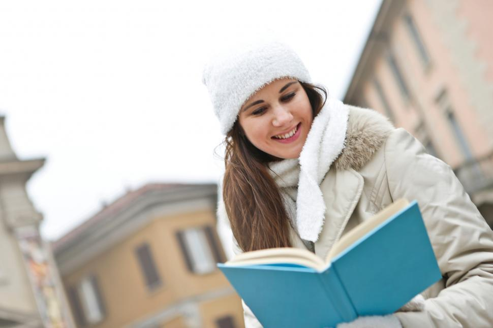 Download Free Stock HD Photo of A young causasian woman reading a book outdoors Online