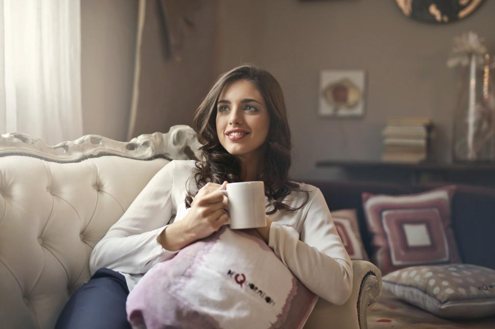 Download Free Stock HD Photo of A young woman sitting on the couch holding a coffee mug in her h Online