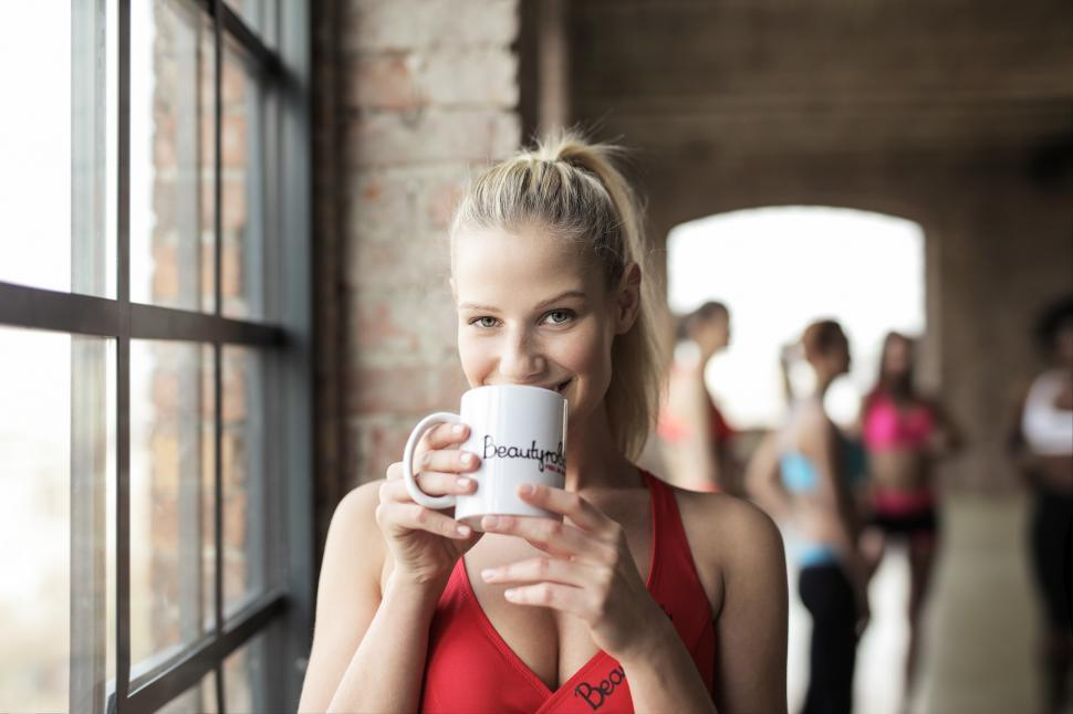 Download Free Stock HD Photo of A young blonde woman wearing red sports bra holding coffee mug i Online